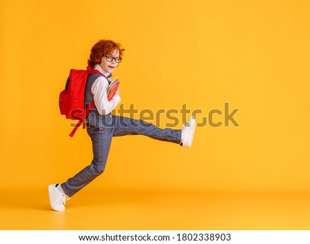 Side view of delighted schoolboy smiling and carrying textbooks while walking to school against yellow backdrop Foto stock ©
