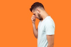 Side view of depressed brunette man with beard in white t-shirt hiding face in hand, looking desperate, is about to cry, empty copy space on left for text. studio shot isolated on orange background