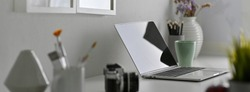 Side view of designer office desk with laptop, painting tools, camera and decorations on white table