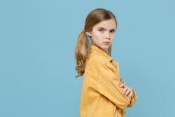Side view of displeased little blonde kid girl 12-13 years old in yellow jacket isolated on blue background. Childhood lifestyle concept. Mock up copy space. Holding hands crossed, looking camera