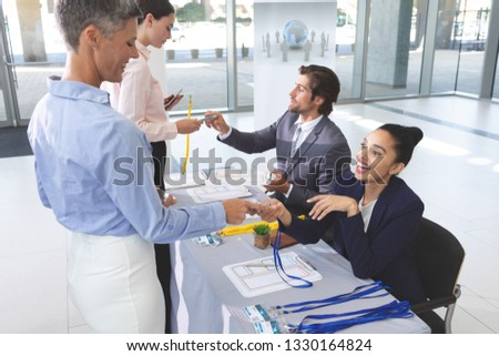 Side view of diverse business people checking in at conference registration table in office lobby