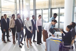 Side view of diverse business people checking in at conference registration table while mixed-race businesswoman wearing hijab looks at table in office lobby