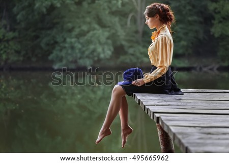 Side view of dreaming girl sitting on jetty forest and river on background. Beautiful woman sitting by the lake. Sad girl depressed sitting on bridge. Lonely woman sitting on a wooden bridge