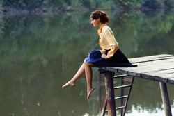Side view of dreaming girl sitting on jetty forest and river on background. Lonely woman on wooden bridge by the lake