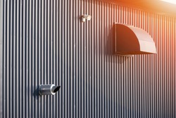 Side view of dryer vent with little megaphone and gas heating boiler flue chimney on grey corrugated metal wall of modern factory building