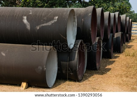 side view of ductile iron pipes stored in open space store yard.