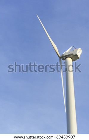 Side view of eco-friendly wind turbine isolated against a blue sky. Nantucket, Massachusetts, USA for Earth Day environmental concept
