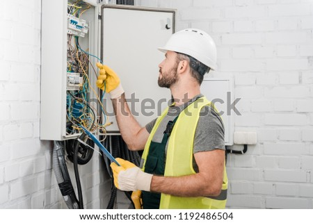 side view of electrician holding clipboard and checking wires in electrical box in corridor