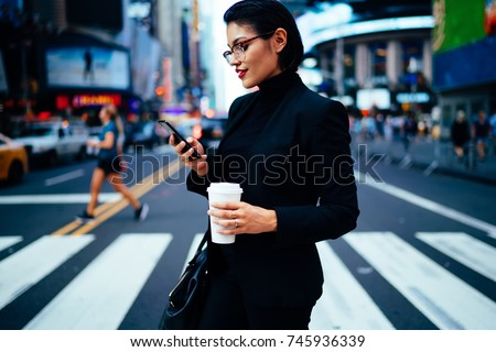 Side view of elegant female entrepreneur reading financial news on phone while passing crosswalk in megalopolis. confident businesswoman crossing street holding coffee to go and texting sms on phone