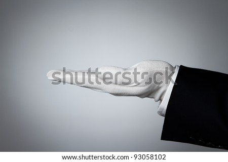 Side view of elegant human hand offering some product