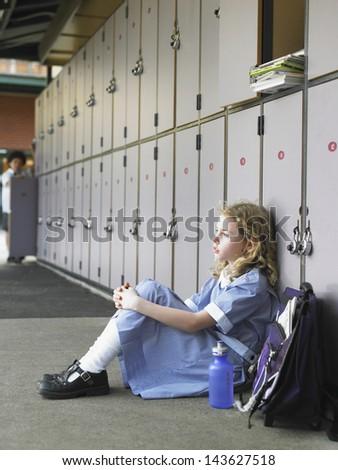 Side view of elementary girl sitting on floor against school lockers
