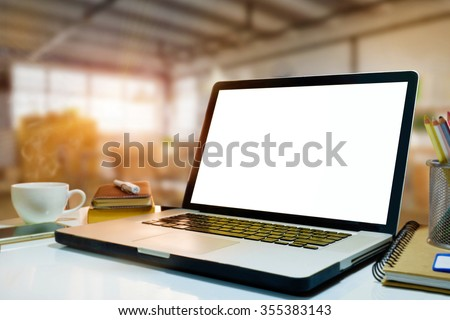 Side view of empty screen laptop on desk work in warehouse background.