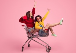 Side view of excited young friends smiling and raising hands while riding shopping trolley against pink background