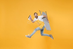 Side view of excited young man househusband in apron rubber gloves hold iron board for ironing while doing housework isolated on yellow background studio. Housekeeping concept. Jumping looking camera