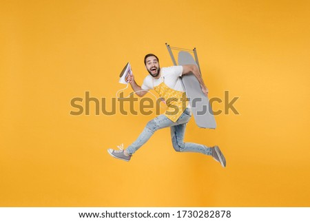 Side view of excited young man househusband in apron rubber gloves hold iron board for ironing while doing housework isolated on yellow background studio. Housekeeping concept. Jumping looking camera ストックフォト ©
