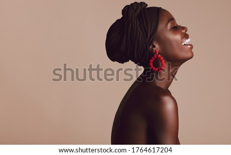 Side view of fashionable african woman smiling on beige background. African female with a turban smiling in studio. Stockfoto ©