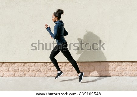 Side view of female athlete running against wall #635109548