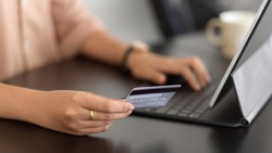 Side view of female holding debit card and using digital tablet for online paying on the table