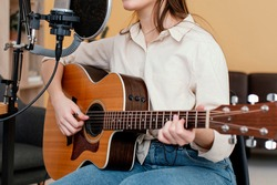 Side view of female musician recording song and playing acoustic guitar at home