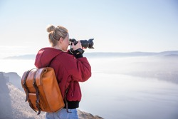 Side view of female photographer with backpack and photo camera taking picture of natural foggy landscape while standing on edge of cliff during trip in United States in sunny day