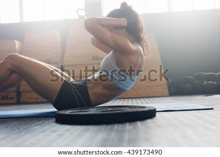 Side view of fit young woman doing pilates, working on abdominal muscles. Fitness woman exercising to improve core muscle strength in gym.