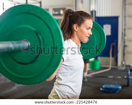 Side view of fit young woman lifting barbell in cross training box