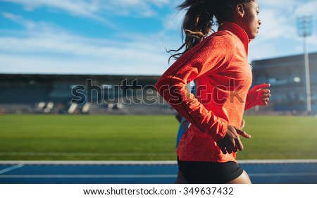 Side view of fit young woman running. African female athlete training on race track at athletics stadium.