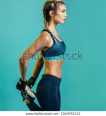 Side view of fitness woman stretching her legs against blue background. Fit female runner doing stretches.