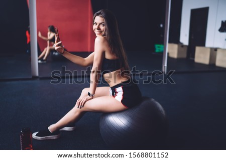 Side view of flirty smiling fit female taking selfie with mobile phone while sitting on exercise ball in gymnastic room and looking over shoulder at camera