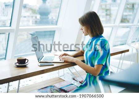 Side view of focused female remote worker with short hair browsing netbook and looking at screen while sitting with coffee cup in light workspace Stock photo ©