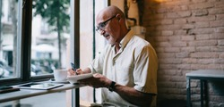 Side view of focused senior bearded male journalist in casual clothes working near window in modern cafe and taking notes in notepad