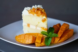 Side view of fresh homemade Filipino mango cake with whipped frosting and spearmint