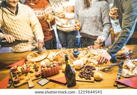 Side view of friends group tasting christmas sweets food and having fun at home drinking champagne sparkling wine - Winter holidays concept with people enjoying time eating together - Warm filter