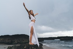 Side view of full length barefoot cheerful female in long dress standing on rocky cliff with raised arms and looking at camera