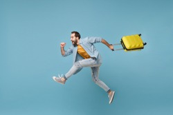 Side view of funny traveler tourist man in yellow clothes isolated on blue background. Male passenger traveling abroad on weekends. Air flight journey concept. Jumping like running, hold suitcase
