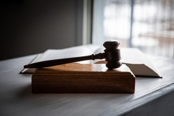 Side view of gavel on block with legal textbook open