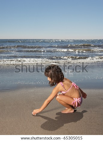 Side view of girl picking up shell on sand at beach