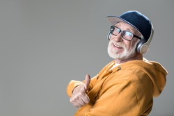 Side view of glad mature man wearing earphones on head. He is giving thumb up. Copy space in left side. Isolated on grey background