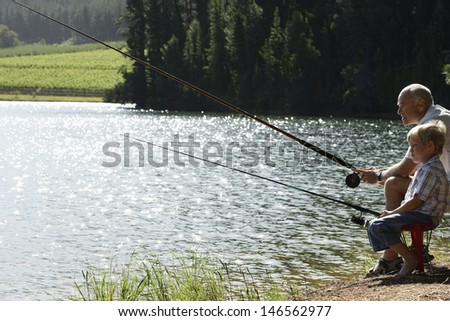 Side view of grandfather and grandson fishing together by lake