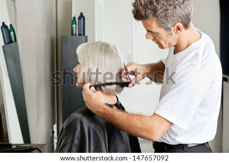 Side view of hairdresser examining hair length of female client at salon