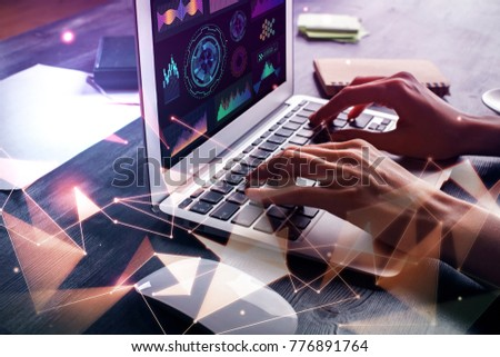 Side view of hand using laptop with abstract digital hologram at office desktop with objects. Future and finance concept. Double exposure