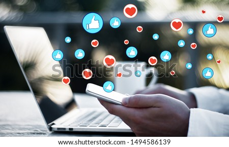 Side view of hands using laptop and cellphone on desktop with emotive on blurry background. Communication and emotion concept