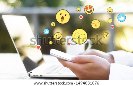 Side view of hands using laptop and smartphone on desktop with emotive on blurry background. Communication and emotion concept