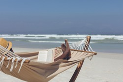Side view of handsome African American man reading book while relaxing on hammock at beach on a sunny day