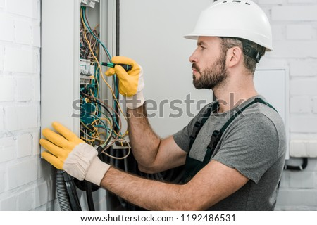 side view of handsome bearded electrician repairing electrical box and using screwdriver in corridor