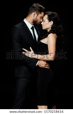 side view of handsome bearded man with closed eyes standing with attractive girl isolated on black  ストックフォト ©