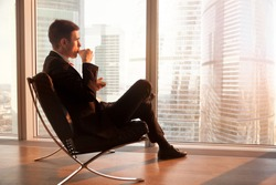 Side view of handsome businessman sitting in comfortable office chair enjoying cup of coffee in the morning, looking through big window at dawn sunrise city, getting motivation for new working day