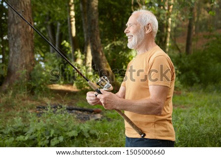 Side view of handsome European male pensioner catching fish against pine trees background, pulling rod with catch out of water, smiling happily, enjoying active outdoor hobby in wild nature #1505000660