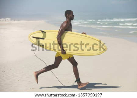 Side view of handsome fit African American male surfer with a surfboard running on beach on a sunny day