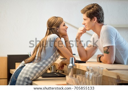 Photo of  side view of handsome man and young woman flirting and smiling each other while working n cafe